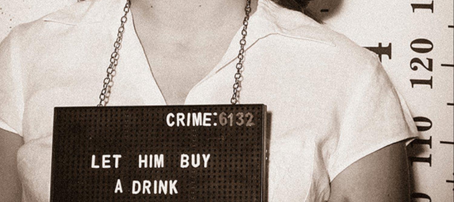 Woman's torso wearing a white blouse. Holding up a sign that says 'Let him buy a drink'