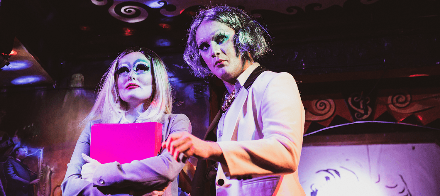 [Two people on a stage, looking out into the audience. Both in suits and drag make-up]