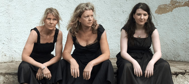 three women in black dresses, sat on bench