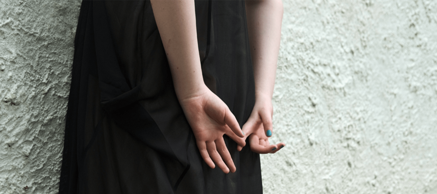 Woman in a black dress holding her hand behind her back.