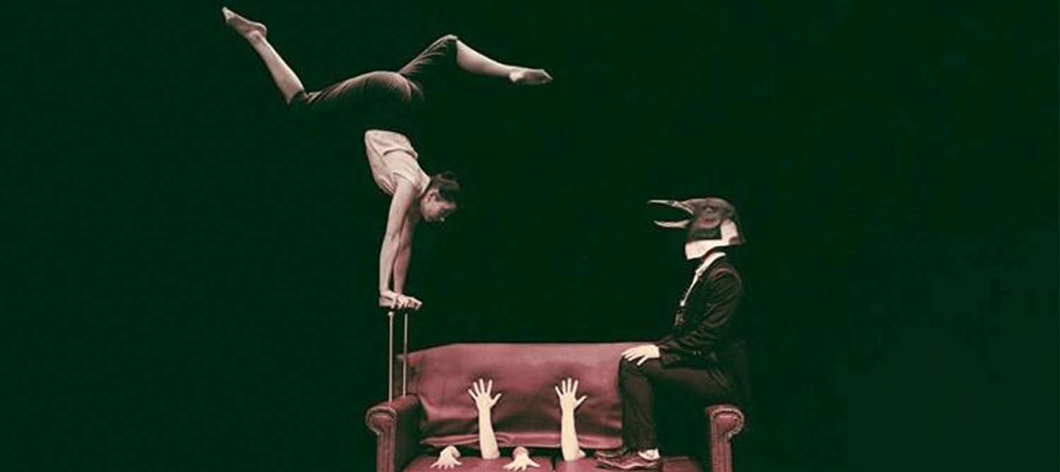 Acrobat balnaced on hands above a sofa besides a figure in a penguin mask