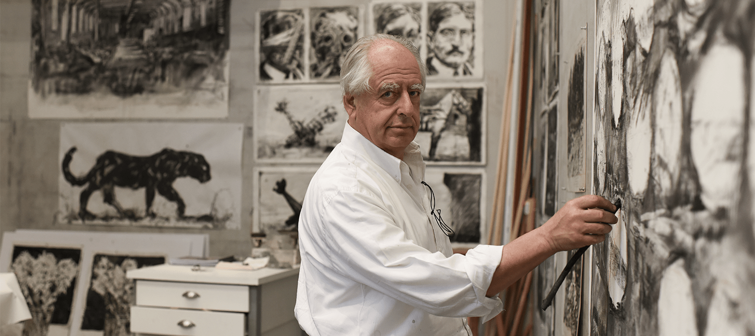 William Knetridge in his studio holding a paintbrush to a piece
