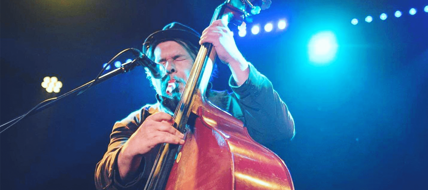 Grant Sharkey Performing with double Bass and microphone.