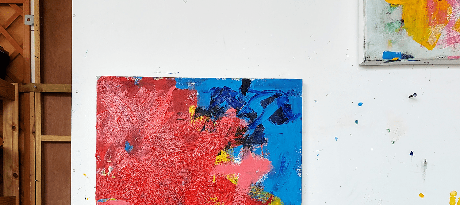 Two abstract paintings hung on a white wall.