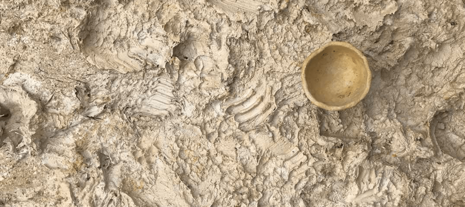 Indents in brown clay with small clay pot.