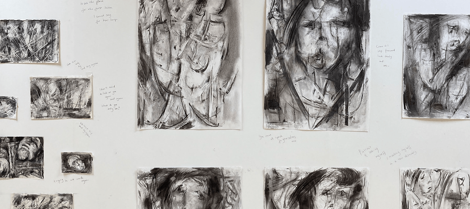 A variety of charcoal drawings on the wall with pencil annotations.