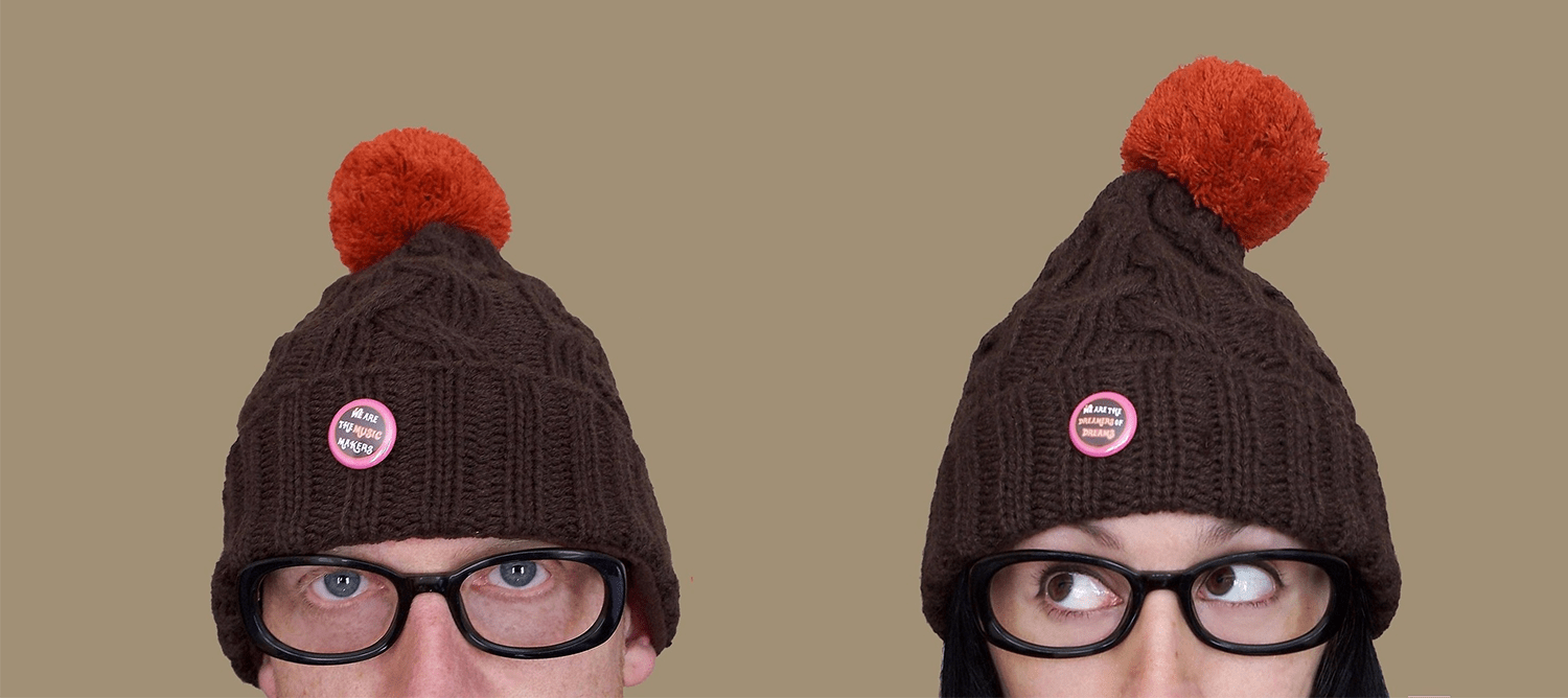 Two people wearing black glasses and beanies with red pom pom.