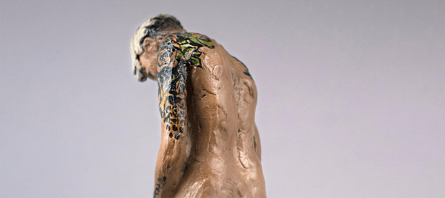 sculpture of human man with back to the picture, head hanging over and tattoos on one arm