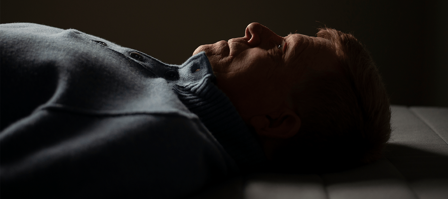 close up image of man lying on floor in dimly lit room