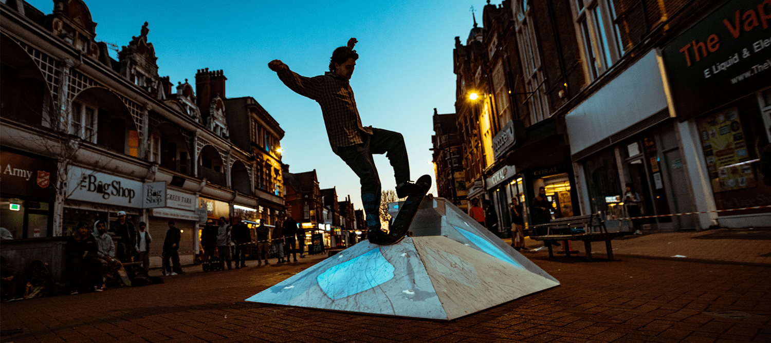 Skateboarder Jumping over a metal ramp in the middle of Boscombe Precinct.