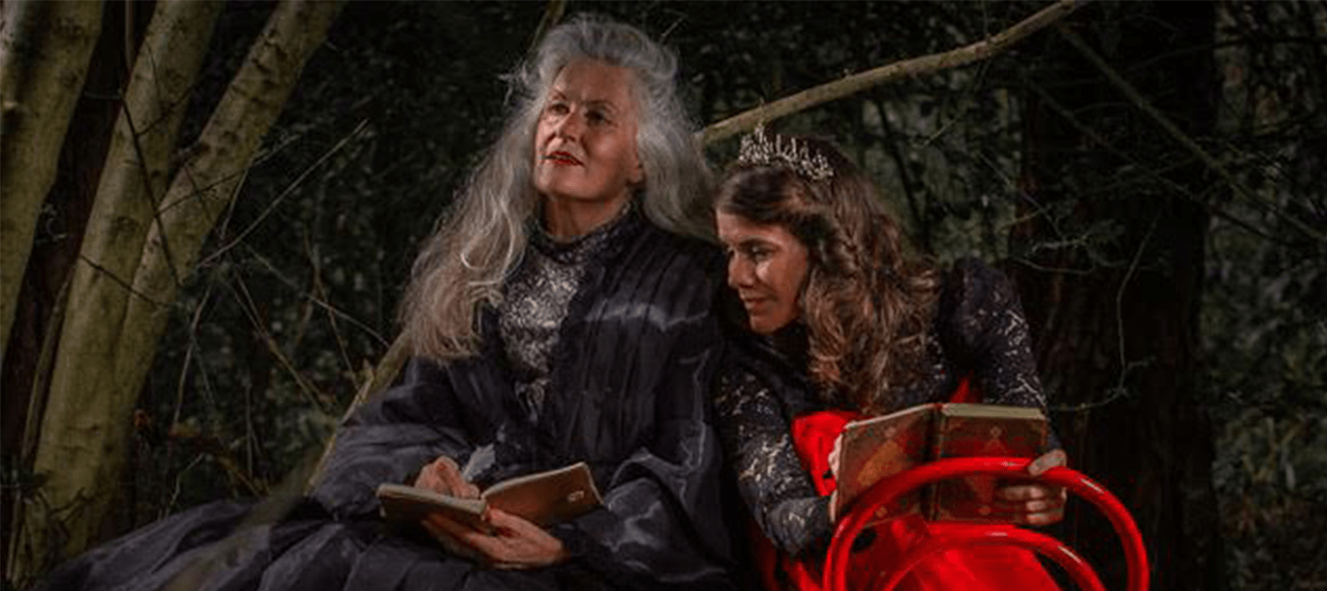 Image depicts two women in a forest reading books