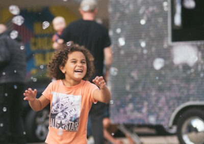 Child laughing as they enjoy the falling bubbles outside
