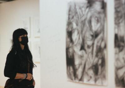 Woman in black wearing mask looking at Ineke Van Der Wal's charcoal drawings