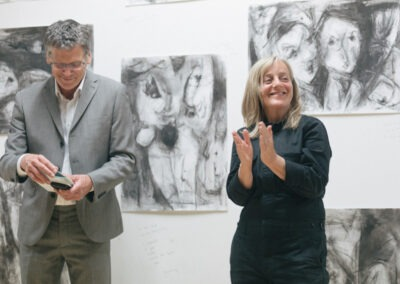 Man and woman stood in front of Ineke Van Der Wal's charcoal drawings