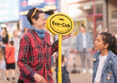 Woman stood with yellow 'Eco Cab' sign smiling at child