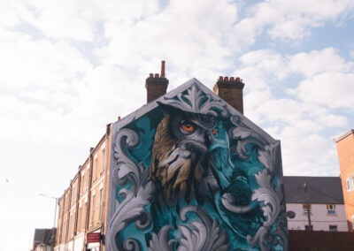 Spray painted owl mural in brown, silver and blue on the side of a building