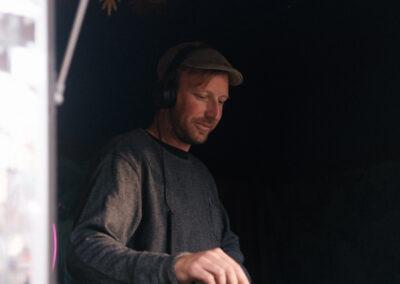 Man with headphones on in using DJ deck