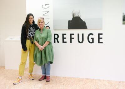 Two women (Jaz O'Hara & Caroline Beale Johnson stood closely in front of the Seeking Refuge installation