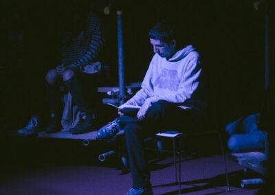 Josh Ward performing 'Being Josh' sat on a chair under a blue spotlight