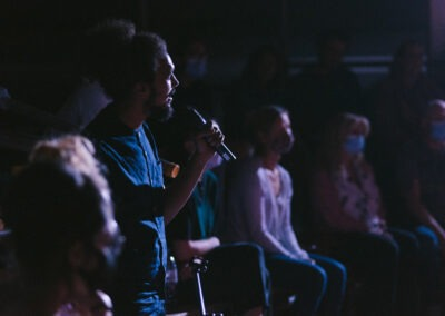 Performer in low theatre lighting with microphone amongst audience