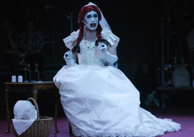 Drag performer in wedding dress sits next to table with wine and pill bottles