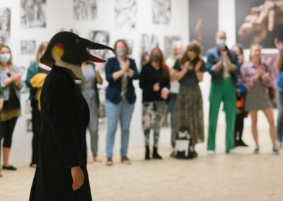 Performer with penguin mask stand in the centre of audience circle