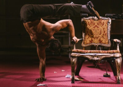Shirtless man performs contortion act with a chair