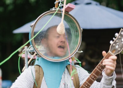 Stuart Faulkner as a one man band playing the guitair with his head in a clear drum