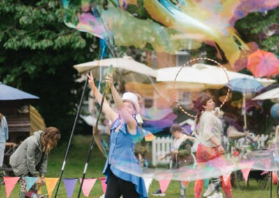 Performer making large bubbles at the Churchill Gardens event