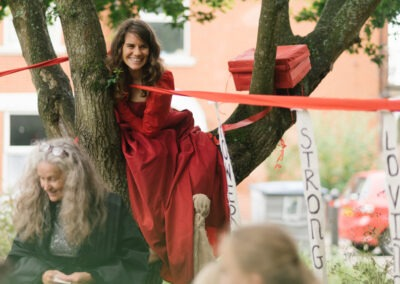Valise Noir female duo sat in a tree with red and white ribbons that read 'Powere' 'Love' and 'Strength'