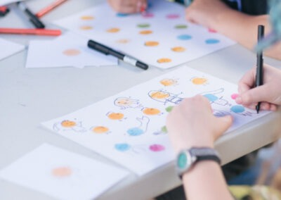 Children drawing coloured circles on paper at a white table