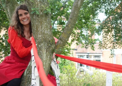 Woman in red sat smiling in a tree